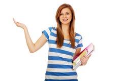 Mujer adolescente que presenta algo en la palma abierta Imágenes de archivo libres de regalías