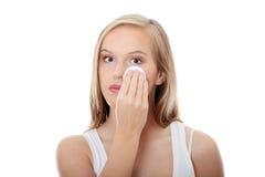 Mujer adolescente que quita maquillaje Foto de archivo libre de regalías