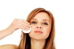Mujer adolescente que quita maquillaje con el cojín de algodón Imagen de archivo
