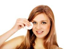 Mujer adolescente que quita maquillaje con el cojín de algodón Fotos de archivo