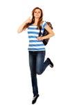 Mujer adolescente que salta con la mochila y el thmb para arriba Fotografía de archivo