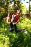 Mujer adolescente que salta en bosque del verano Imagen de archivo