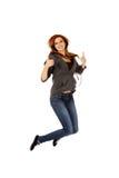 Mujer adolescente que salta mostrando los pulgares para arriba Imágenes de archivo libres de regalías