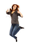 Mujer adolescente que salta mostrando los pulgares para arriba Fotografía de archivo libre de regalías