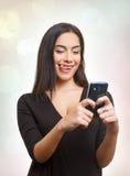 Mujer adolescente que se divierte con el teléfono móvil Foto de archivo libre de regalías