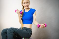 Mujer adolescente que se resuelve en casa con pesa de gimnasia Fotografía de archivo