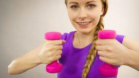 Mujer adolescente que se resuelve en casa con pesa de gimnasia Fotos de archivo libres de regalías