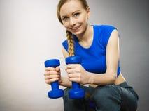 Mujer adolescente que se resuelve en casa con pesa de gimnasia Imágenes de archivo libres de regalías