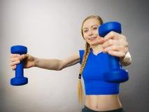 Mujer adolescente que se resuelve en casa con pesa de gimnasia Fotos de archivo