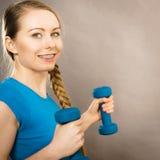 Mujer adolescente que se resuelve en casa con pesa de gimnasia Imagen de archivo libre de regalías