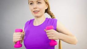 Mujer adolescente que se resuelve en casa con pesa de gimnasia Imagenes de archivo