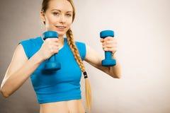 Mujer adolescente que se resuelve en casa con pesa de gimnasia Foto de archivo