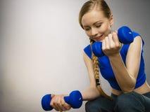 Mujer adolescente que se resuelve en casa con pesa de gimnasia Imagen de archivo