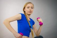 Mujer adolescente que se resuelve en casa con pesa de gimnasia Fotografía de archivo libre de regalías