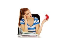 Mujer adolescente que se sienta detrás del escritorio y que sostiene el despertador Imagen de archivo libre de regalías
