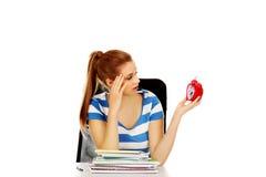 Mujer adolescente que se sienta detrás del escritorio y que sostiene el despertador Foto de archivo