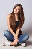 Mujer adolescente que se sienta en piso Fotografía de archivo libre de regalías