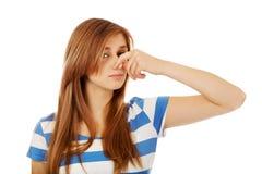 Mujer adolescente que se sostiene la nariz debido a un mún olor fotos de archivo libres de regalías