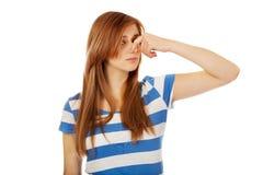 Mujer adolescente que se sostiene la nariz debido a un mún olor fotografía de archivo libre de regalías
