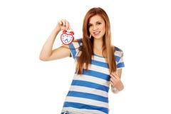 Mujer adolescente que sostiene el despertador Fotografía de archivo
