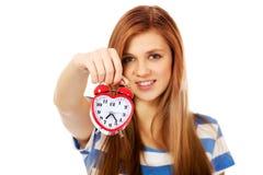 Mujer adolescente que sostiene el despertador Imágenes de archivo libres de regalías
