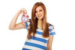 Mujer adolescente que sostiene el despertador Foto de archivo libre de regalías