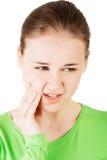 Mujer adolescente que tiene un dolor terrible del diente. Fotos de archivo