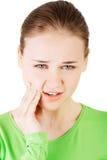 Mujer adolescente que tiene un dolor terrible del diente. Fotografía de archivo