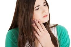 Mujer adolescente que tiene un dolor terrible del diente Foto de archivo