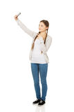 Mujer adolescente que toma selfies con el teléfono elegante Fotografía de archivo libre de regalías