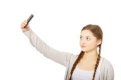 Mujer adolescente que toma selfies con el teléfono elegante Imágenes de archivo libres de regalías