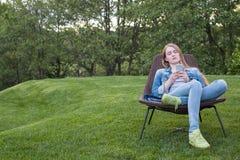 Mujer adolescente que usa smartphone fuera del jardín Fotos de archivo libres de regalías