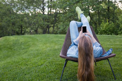 Mujer adolescente que usa smartphone fuera del jardín Imagenes de archivo