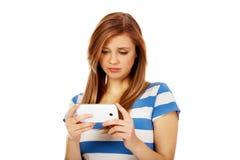 Mujer adolescente que usa su smartphone Imagen de archivo