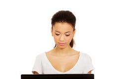 Mujer adolescente que usa un ordenador portátil Foto de archivo