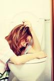Mujer adolescente que vomita en retrete Foto de archivo libre de regalías