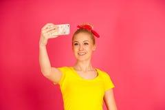 Mujer adolescente rubia joven hermosa en la camiseta amarilla que toma el SE Fotos de archivo