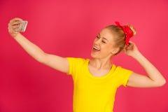 Mujer adolescente rubia joven hermosa en la camiseta amarilla que toma el SE Imagen de archivo