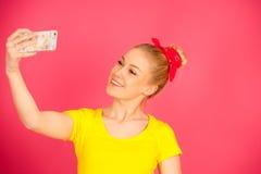 Mujer adolescente rubia joven hermosa en la camiseta amarilla que toma el SE Imágenes de archivo libres de regalías
