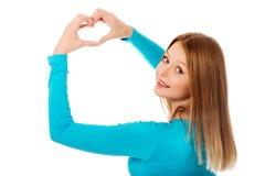 Mujer adolescente sonriente que hace forma del corazón Foto de archivo