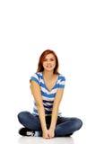 Mujer adolescente sonriente que se sienta en un piso con las piernas cruzadas fotografía de archivo libre de regalías