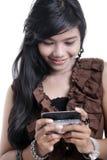 Mujer adorable asiática que usa el adminículo foto de archivo