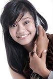 Mujer adorable asiática que usa el adminículo fotografía de archivo libre de regalías