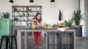 Mujer adorable del jengibre que lee el libro culinario y que baila en la cocina, colocándose con sus codos en la tabla, señora re metrajes