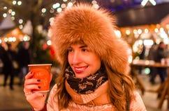 Mujer adorable en el mercado del invierno que disfruta del coffe caliente Fotos de archivo