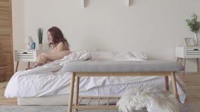 Mujer adorable que miente en cama por la mañana Señora sonriente que se relaja en casa Ocio dentro, día libre Caucásico feliz almacen de metraje de vídeo