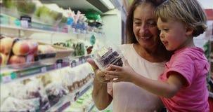 Mujer adulta con el niño que hace compras junto almacen de video
