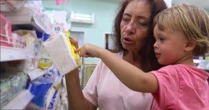 Mujer adulta con el niño que hace compras junto metrajes