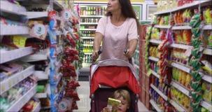 Mujer adulta con el niño que hace compras junto almacen de metraje de vídeo