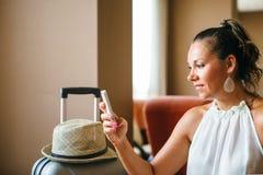 Mujer adulta con la cola de caballo usando smartphone imagen de archivo